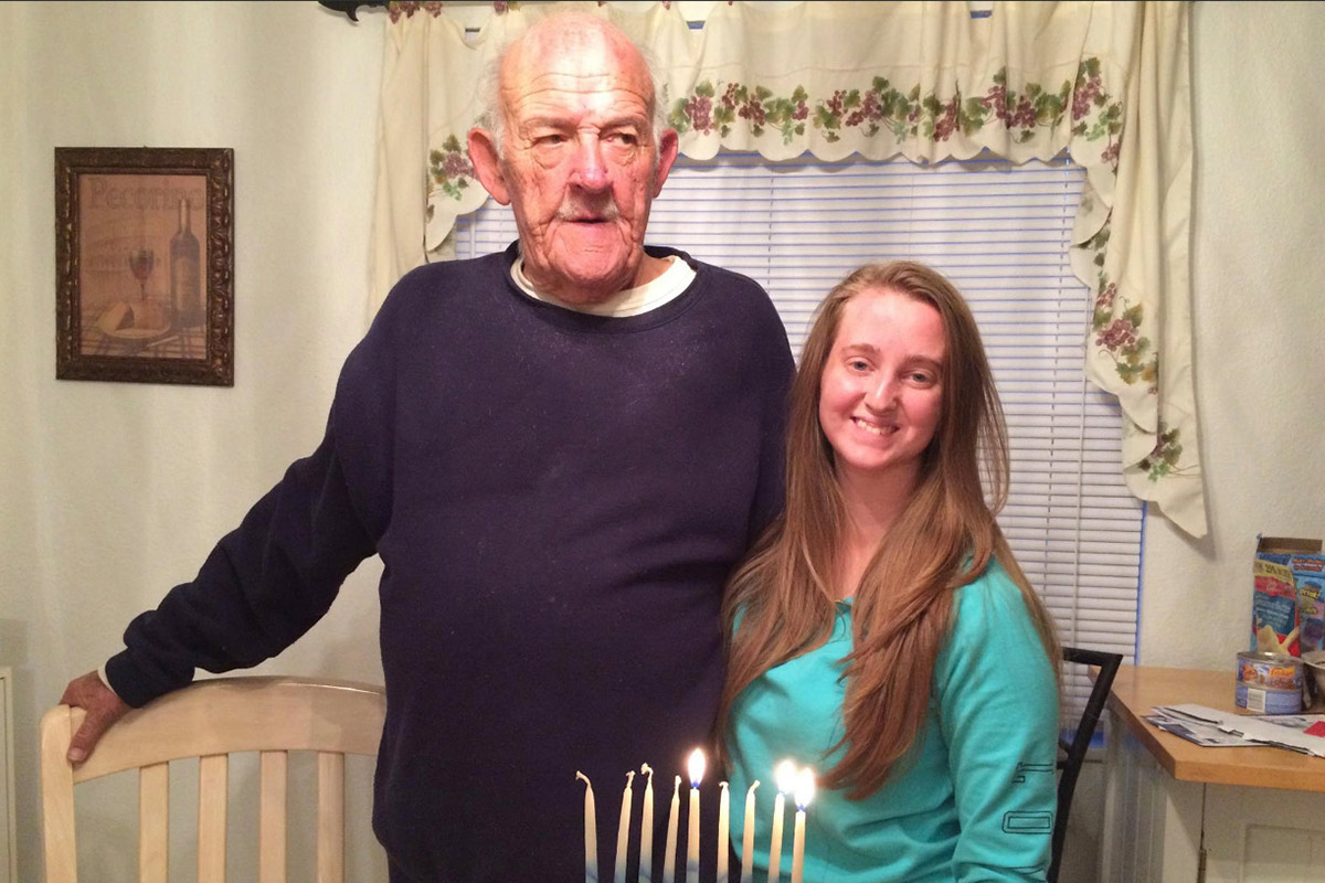 Ashley and her poppy lighting Hanukkah candles