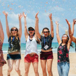Birthright Israel participants jumping and throwing biodegradable confetti in the air on a beach in Haifa