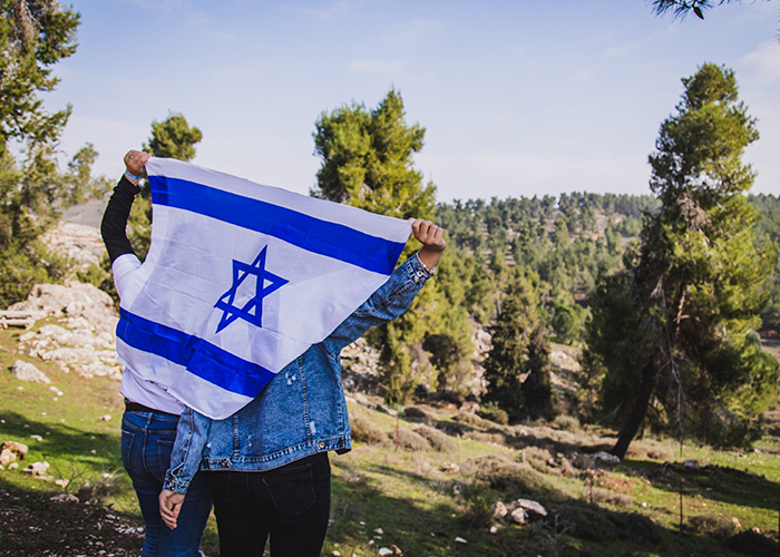 Birthright Israel participants holding an Israeli flag