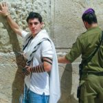 David Bitton, 2006 Birthright Israel Alumnus, with his hand on the Western Wall next to an Israeli soldier