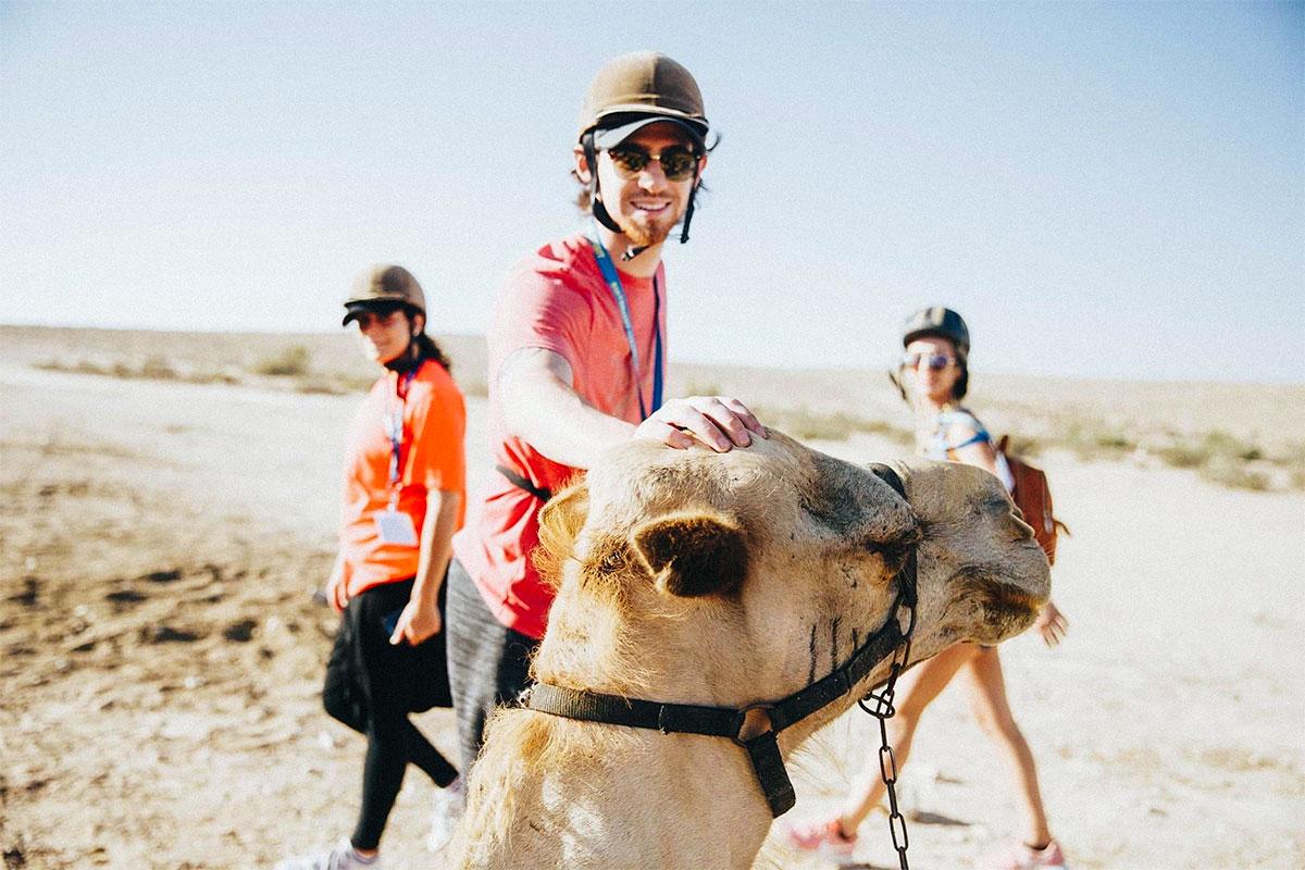 Matt riding a camel in the Negev