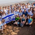Birthright Israel participants holding an Israeli flag.