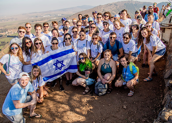 Birthright Israel participants holding an Israeli flag.