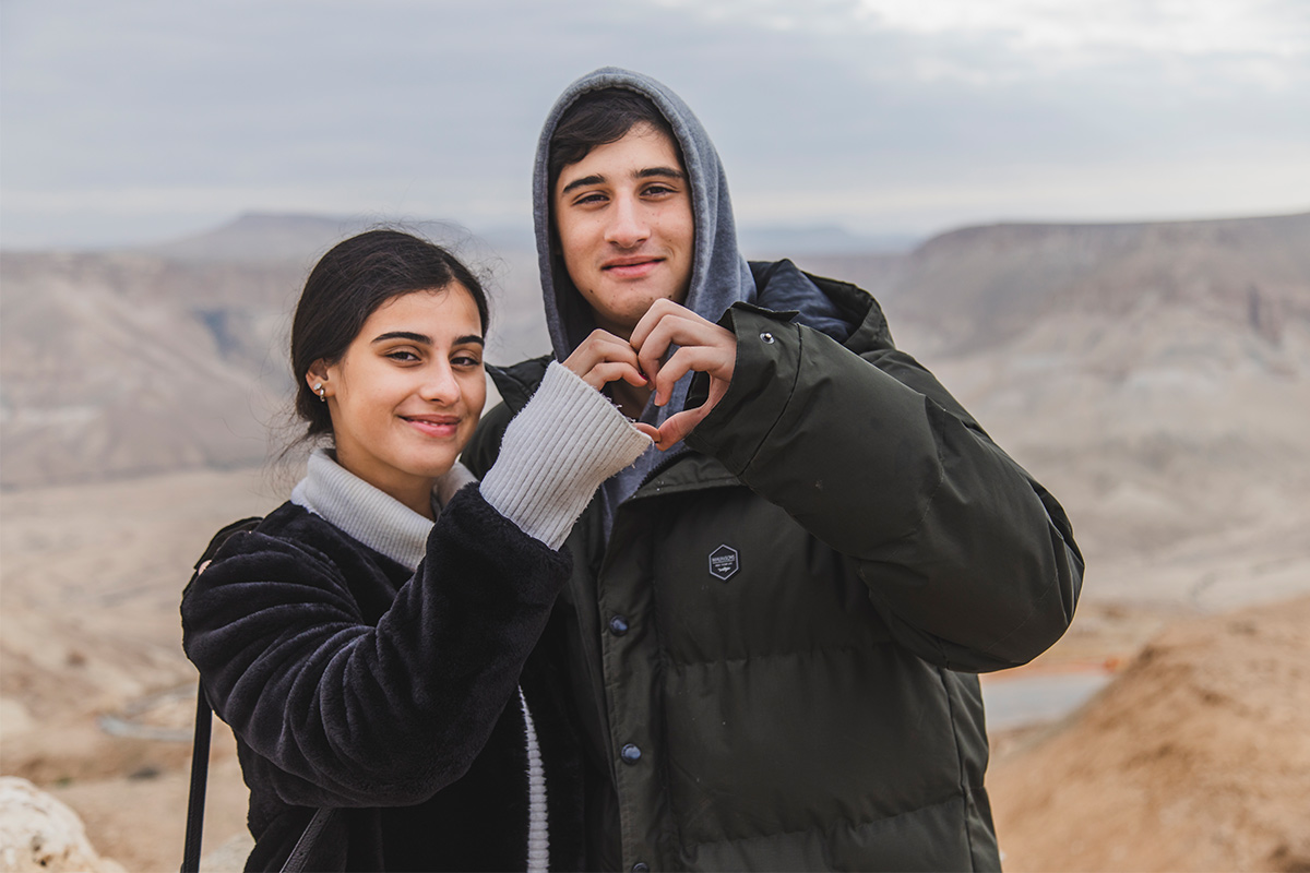Birthright Israel participants holding their hands in the shape of a heart.