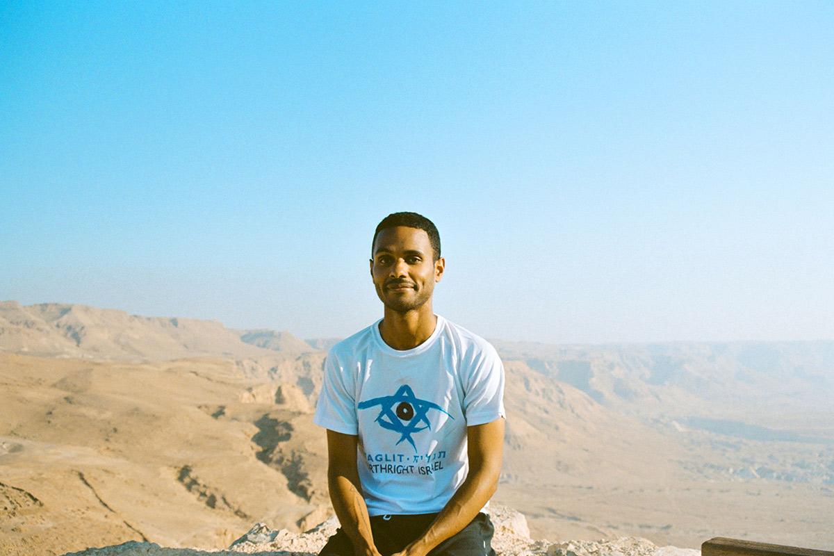 Birthright Israel alumnus Luis Burgos sitting atop Masada