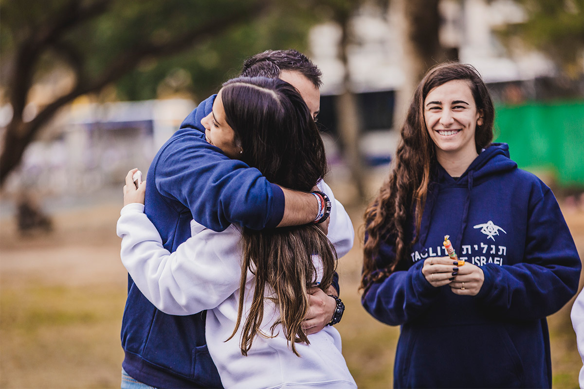 Two Birthright Israel participants hugging.