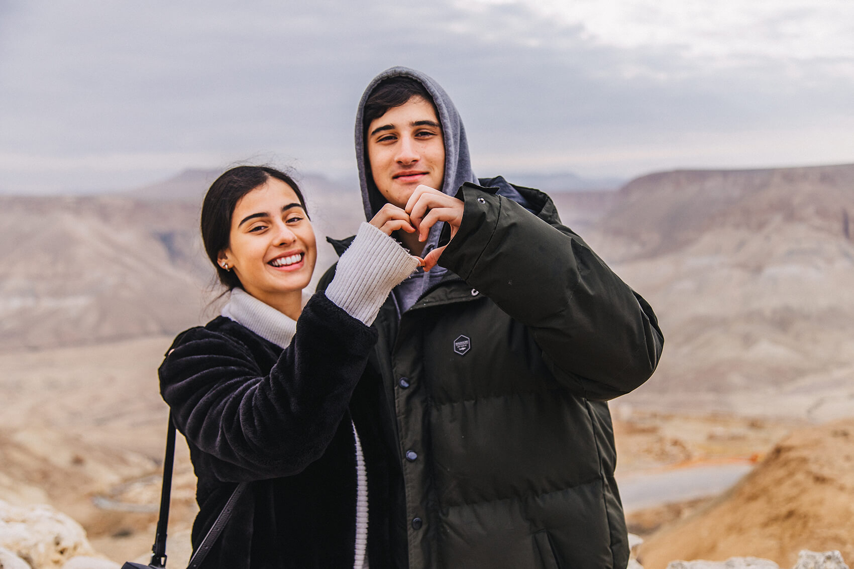 Two Birthright Israel participants forming a heart with their hands in the Negev)
