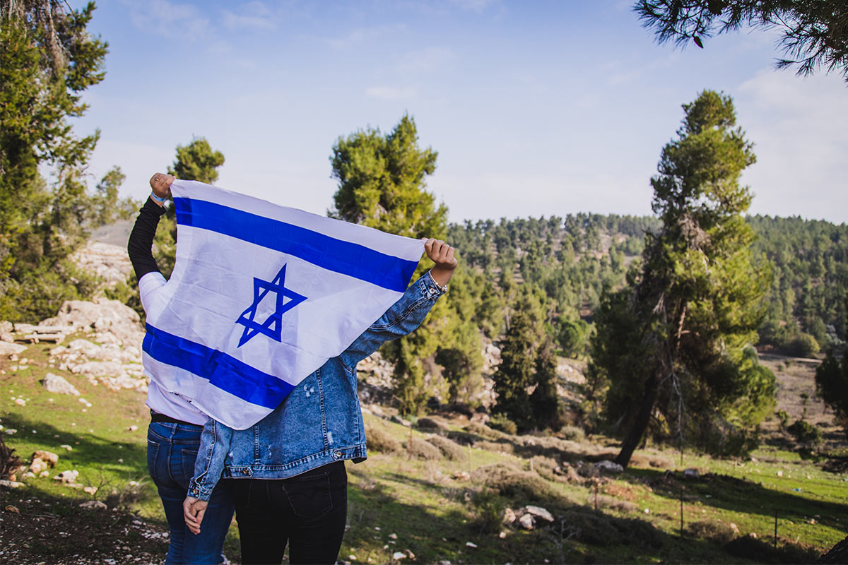 Birthright Israel participants holding a flag overlooking greenery.