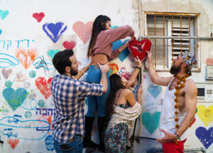 A group of Birthright Israel participants decorating a wall with hearts in Tel Aviv