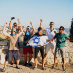 A group of Jewish American Birthright Israel participant holding the Israeli flag