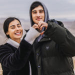 Two Birthright Israel participants forming a heart with their hands on top of Masada