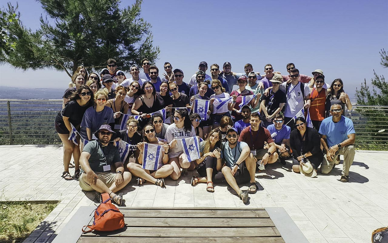 Cooper Myers with his 2019 Birthright Israel group holding Israeli flags