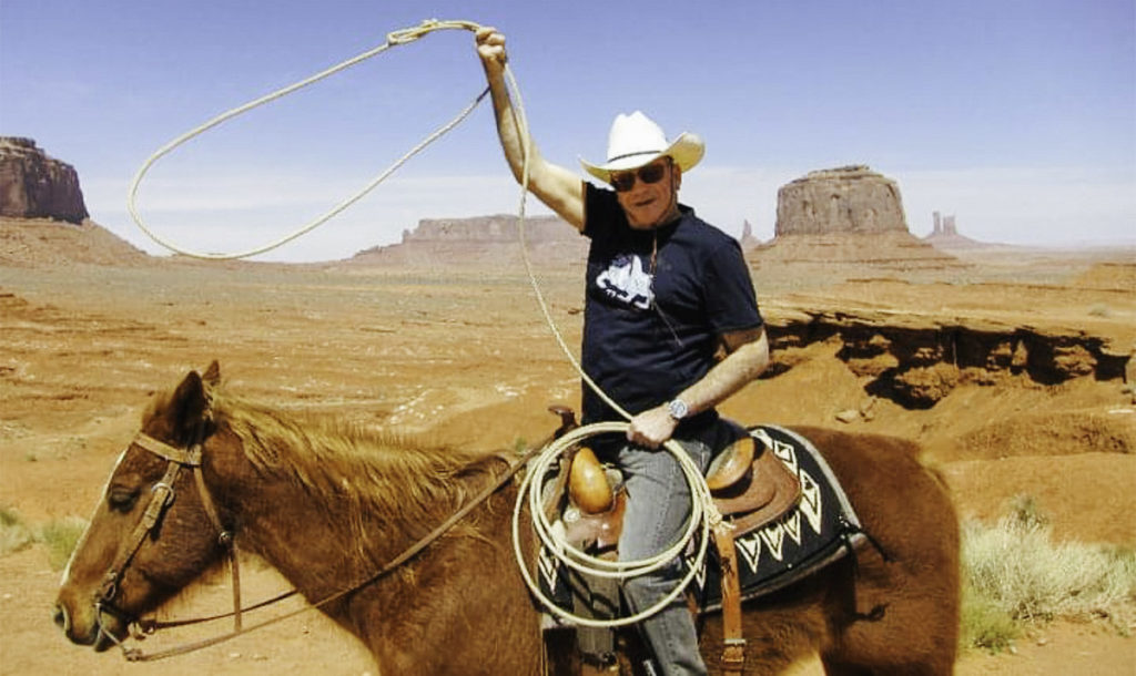 Robert Beleson on horseback spinning a rope lasso over his head in the desert