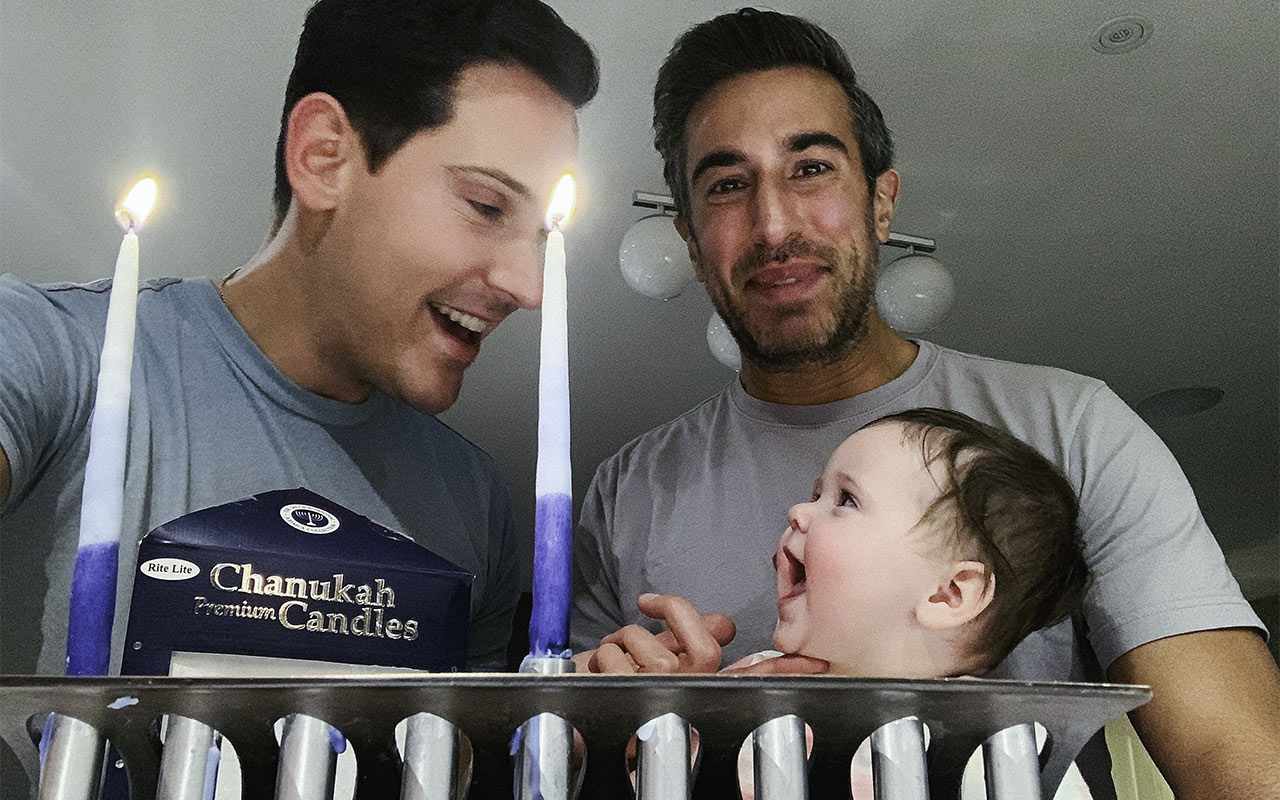 David and his husband Oren with their daughter on the first night of Chanukah