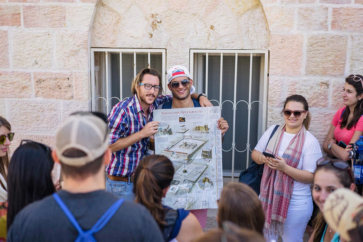 A Birthright Israel staff member and tour educator speak to participants.